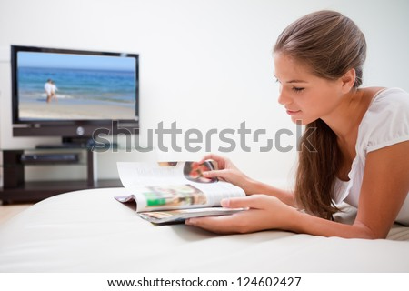 Young woman in the living room reading magazine - stock photo