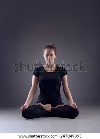 Young woman in the lotus pose - stock photo