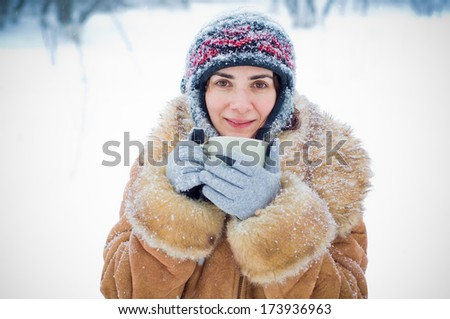 Young woman in the snow with a mug - stock photo