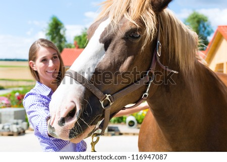 Young woman in the stable with horse, caring and is happy - stock photo