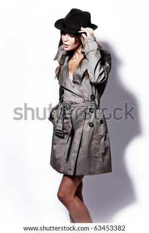 young woman in topcoat and  black hat, studio shot - stock photo