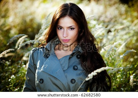 young woman in topcoat walking accros the autumn meadow - stock photo