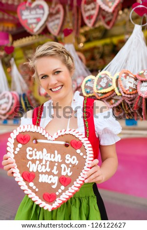 Young woman in traditional Bavarian clothes - dirndl or tracht -with a gingerbread souvenir heart on a festival or Oktoberfest - stock photo