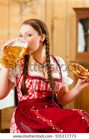 Young woman in traditional Bavarian Tracht in restaurant or pub with beer and steins and pretzel - stock photo