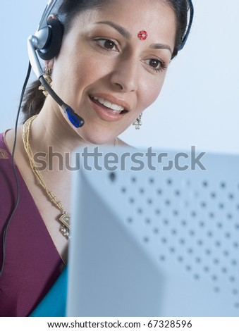 Young woman in traditional Indian dress with headset - stock photo