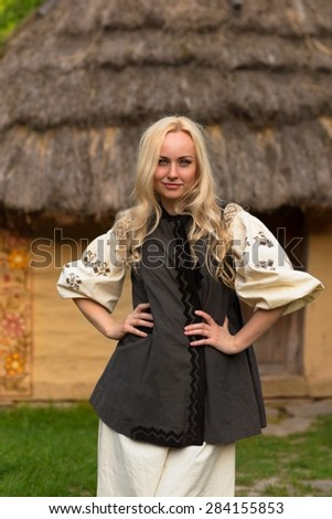 Young woman in ukrainian national costume near old historic house - stock photo