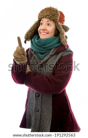 Young woman in warm clothing and pointing upward - stock photo