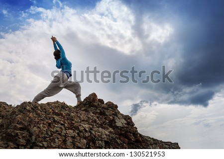 Young woman in warrior yoga pose standing on mountain rock under beautiful cloudy sky. - stock photo