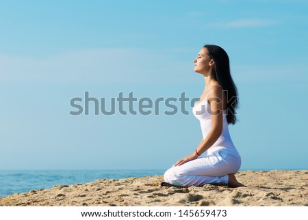 Young woman in white clothes meditating on the beach, portrait in profile - stock photo