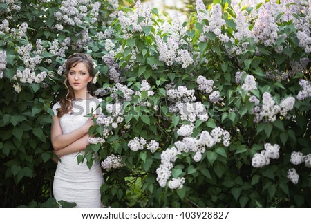 Young woman in white dress embracing herself while standing in white lilac garden - stock photo