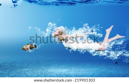 Young woman in white dress swimming under water - stock photo