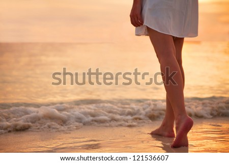 Young woman in white dress walking alone on the beach in the sunset - stock photo
