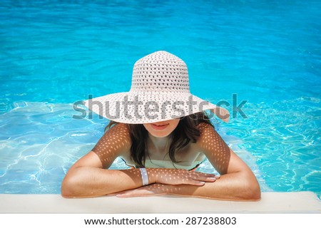 young woman in white hat resting in pool. - stock photo