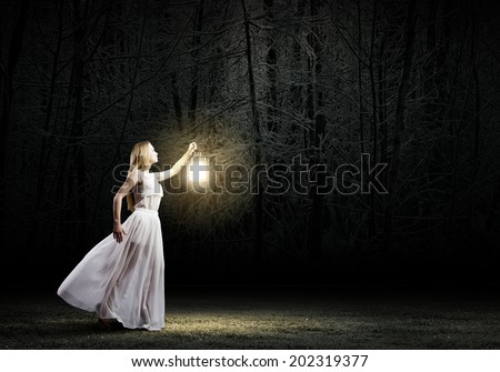 Young woman in white long dress walking in night wood - stock photo