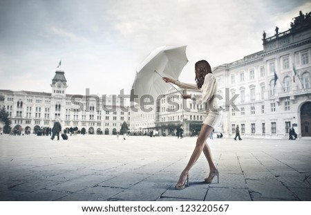 Young woman in white opening a white umbrella - stock photo