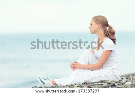 young woman in white relax resting on the sea on the beach - stock photo