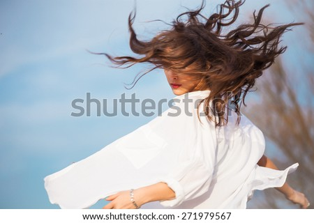 young woman in white shirt with hair in motion, outdoor spring day, blue sky in background - stock photo