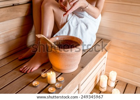 Young woman in white towel pouring water while resting in Finnish sauna - stock photo