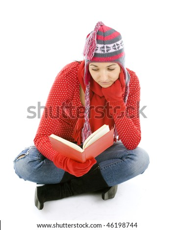 young woman in winter clothes sitting on the floor with crossed legs and reading book - stock photo