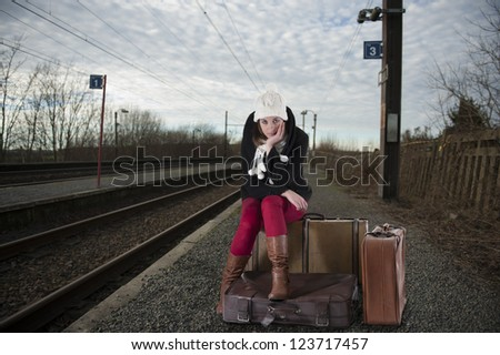 young woman in winter clothes waiting for her train - stock photo