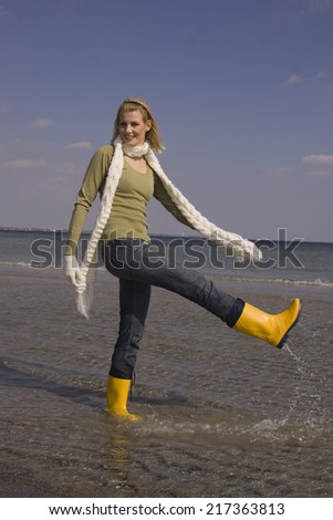 Young woman in winter clothing and boots splashing water at the beach - stock photo
