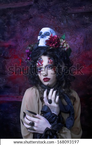 Young woman in witch image with bloody makeup ann with skull. - stock photo