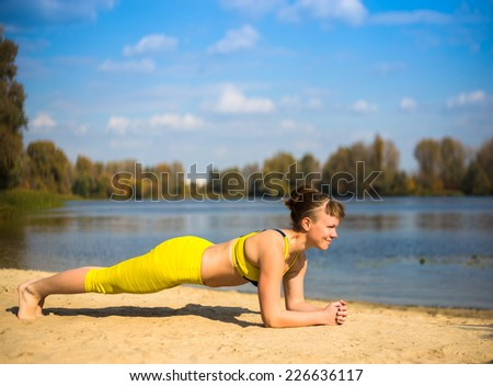 Young woman in yellow clothing doing yoga on the river bank - stock photo