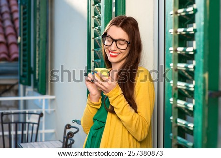 Young woman in yellow sweater and glasses using mobile phone on the balcony with window shutters in old building. - stock photo