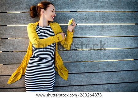 Young woman in yellow sweater using yellow phone on wooden sunbed, top view with space for your text - stock photo