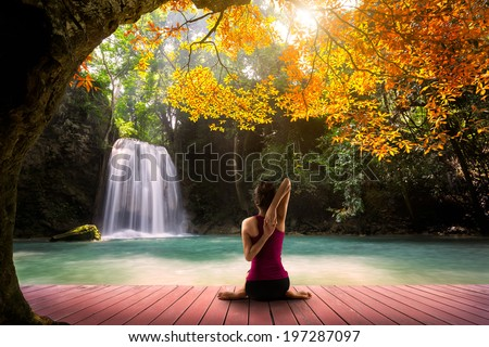 Young woman in yoga Cow face pose sitting near waterfall, Rear view - stock photo