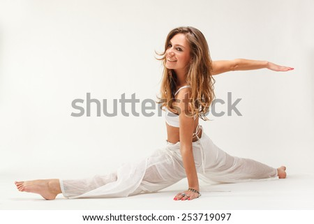 Young woman in yoga pose in studio on white background - stock photo