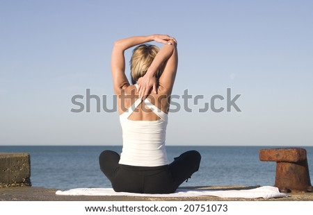 Young woman in yoga position next to the sea - stock photo