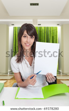 Young woman in zen interior pointing with her pen to a blank paper. Ideal for inserting your own message - stock photo