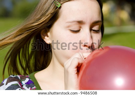 Young woman inflating red balloon - stock photo