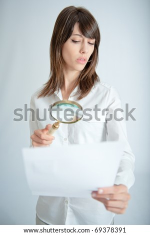 Young woman inspecting closely a document through a magnifying glass - stock photo