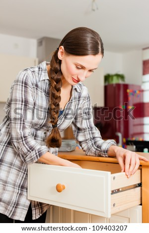 Young woman is assembling a cupboard because she is moving in or out - stock photo