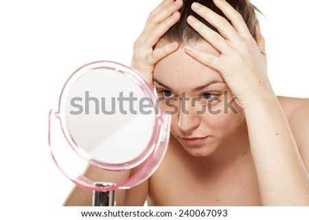 young woman is bored and looking at herself in the mirror - stock photo