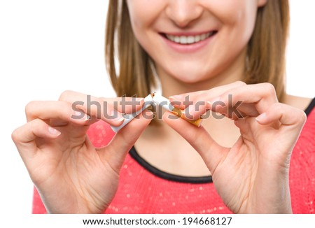 Young woman is breaking a cigarette, quit smoking concept, isolated over white - stock photo