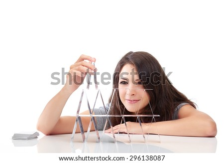 Young woman is building a house of cards on isolated background - stock photo