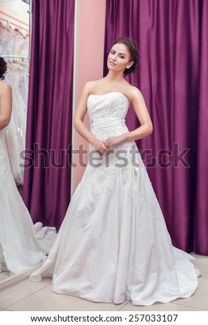 Young woman is choosing a wedding dress in the shop - stock photo