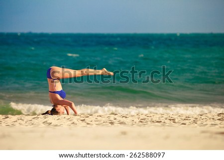 young woman is doing yoga near the sea, standing on her head - stock photo