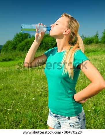 Young woman is drinking water from plastic bottle outdoors - stock photo