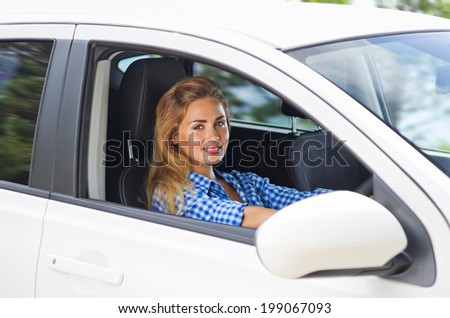 Young woman is driving car - stock photo