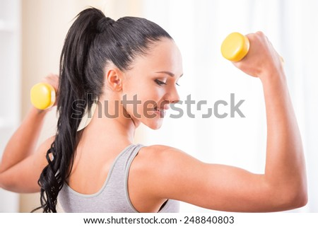 Young woman is exercising with dumbbells at home. Fitness, workout, healthy living and diet concept. - stock photo