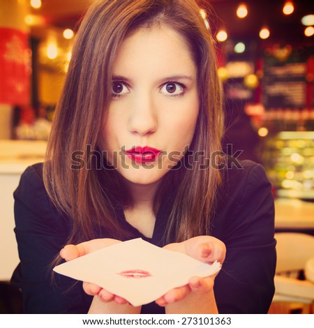 young woman is flirting and blowing kiss on serviette in modern cafe - stock photo