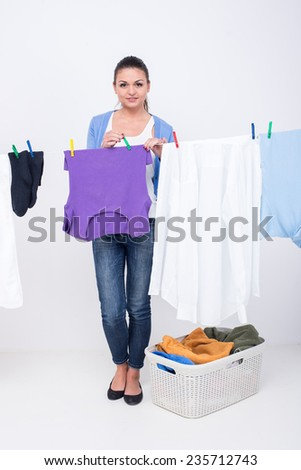 Young woman is hanging clothing on clothesline on white background. - stock photo