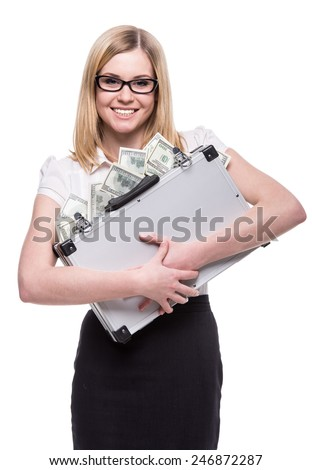 Young woman is holding a suitcase full of money, isolated on white background. - stock photo