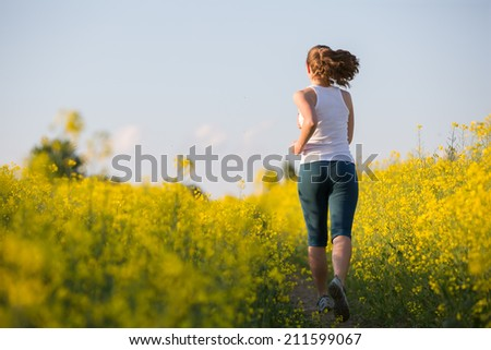 Young woman is jogging in yellow rapeseed field at sunset - stock photo