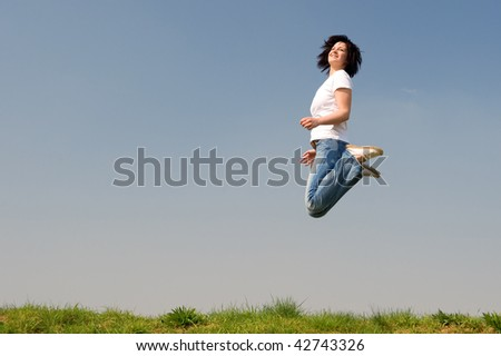 Young woman is jumping over a green - stock photo