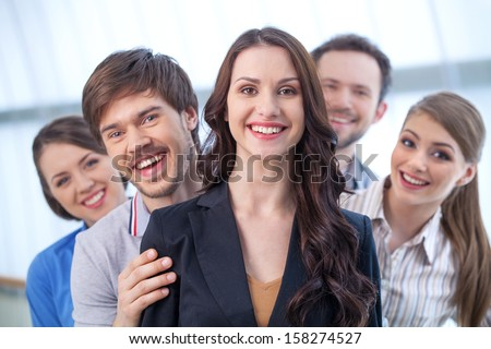 Young woman is leading a group of people. Looking at camera with big toothy smile  - stock photo